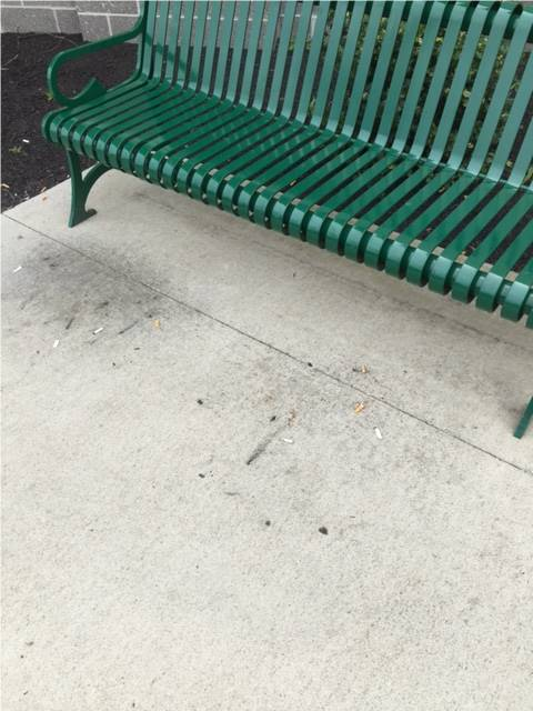 A bench outside a business with cigarette butts and other small trash littered across the ground.